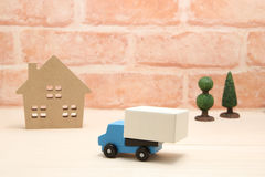 Toy car truck and house in front of brick wall. Royalty Free Stock Images