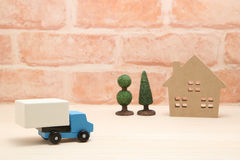 Toy car truck and house in front of brick wall. Royalty Free Stock Photo