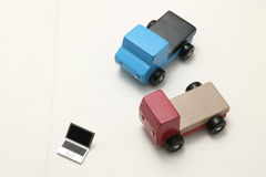 Toy car trucks and miniature laptop on notebook. Internet shopping, on line purchase, e-commerce and packages delivery concept Royalty Free Stock Photo