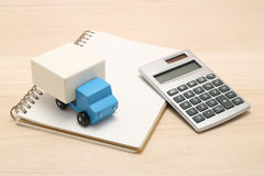 Toy car trucks, a notebook, and a calculator on wood. Stock Photography