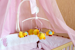 Toy carousel on the cot with orange linen Royalty Free Stock Image