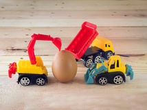 Toy cars take care of egg on wood floor. Egg with toys car on wood floor bussiness concept Stock Photography