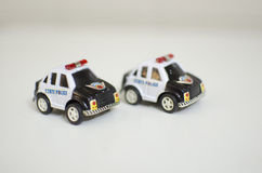 Toy cars. Two little police toy cars royalty free stock image