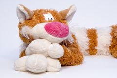 Toy cat. Big soft tabby goggleeyed red-haired cat over white Royalty Free Stock Image