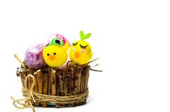 Toy chicken and Easter eggs in wicker nest. Isolated Stock Image