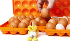 Toy chicken sits in front of orange container with eggs Royalty Free Stock Photos