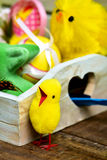 Toy chicks, and decorated easter eggs. Closeup of some some toy chicks and some different decorated easter eggs in a rustic wooden tray, on a wooden surface Stock Image
