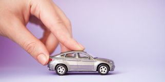 Toy child car in woman`s hand. Purchase insurance bank loan travel where to go trip journey concept. on violet stock photography