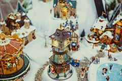 Toy Christmas ceramic miniature with snow-covered city and model of walking people. Small festive village with clock tower. Retro stock photo