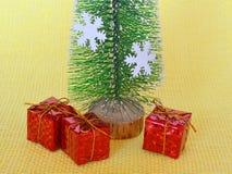 Toy Christmas-de giften dichtbij een stuk speelgoed Kerstboom met witte sneeuwvlokken zijn op een gele weefselachtergrond stock fotografie