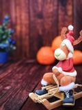 Toy Christmas reindeer in Christmas clothes sitting on a wooden sledge Stock Photo