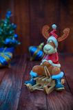 Toy Christmas reindeer in Christmas clothes sitting on a wooden. Sledge, brown wooden background with ornaments Royalty Free Stock Images