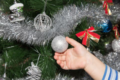 Toy on the Christmas tree in a child`s hand Royalty Free Stock Photo