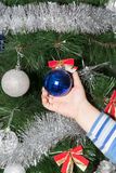 Toy on the Christmas tree in a child`s hand Stock Image