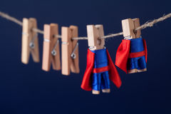 Toy clothespin peg superheroes in suit and red cape. Big small super team characters on dark blue background. soft focus. Toy clothespin peg superheroes in blue stock photos