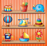 Toy collections that are properly arranged in the wooden shelves Stock Image