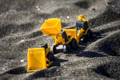 Toy construction machinery in black sand. Yellow and black colors toy machines. Bulldozer, loader, excavator Royalty Free Stock Photos