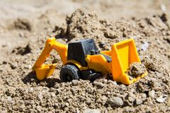 Toy construction machinery in black sand. Yellow and black colors toy machines. Bulldozer, loader, excavator Royalty Free Stock Photo