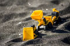 Toy construction machinery in black sand. Yellow and black colors toy machines. Bulldozer, loader, excavator Royalty Free Stock Images