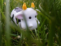 Toy cow is eating grass Stock Photo