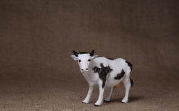 Toy cow on hessian (burlap) cloth Stock Image