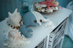 Toy crab and sea shells on a blue dresser Royalty Free Stock Photos