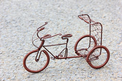 Toy crafts bicycle made of copper wire. On the ground Stock Image