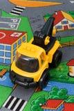 Toy crane. Yellow toy crane on a children's room floor stock photography