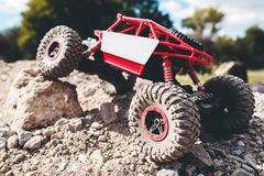 Toy crawler overcoming rock close-up. Rc offroad car riding rocky landscape. Buggy, rally, leisure, entertainment concept Royalty Free Stock Image