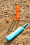 Toy cricket set on beach. Bright orange toy cricket set on beach with shadow approaching viewer Royalty Free Stock Images