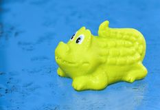 Green crocodile toy is on wet blue background. Toy crocodile in water drops is on the blue background as a symbol of travel stock images