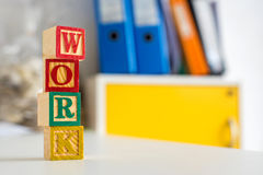 Toy cubes are used to create the word work. Stock Images