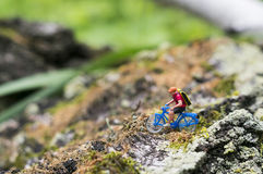 Toy cyclist ecotourism concept. A toy cyclist is taking a ride on the bark of a tree, which covered with moss. Ecotourism concept Stock Images