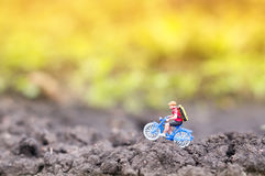 Toy cyclist ecotourism concept. A toy cyclist is taking a ride in the sunset or the sunrise. Ecotourism concept stock photography