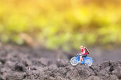 Toy cyclist ecotourism concept. A toy cyclist is taking a ride in the sunset or the sunrise. Ecotourism concept royalty free stock photos