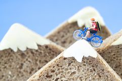 Toy cyclist ecotourism concept. A toy cyclist is taking a ride on mountains, made of healthy rye bread and creamy cheese. Ecotourism and healthy eating concept royalty free stock image