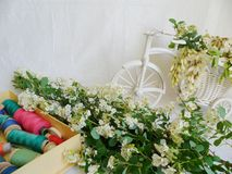 Toy decorated bicycle with white flowers and multi-colored thread for sewing on a white background.  Stock Image