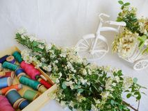Toy decorated bicycle with white flowers and multi-colored thread for sewing on a white background.  Royalty Free Stock Image