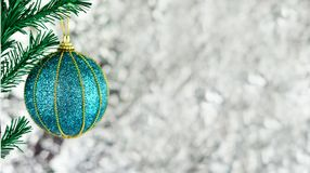 Toy decoration blue ball with a gold pattern. Near the branches of a Christmas tree on a Christmas tree on a bright bokeh background Royalty Free Stock Images