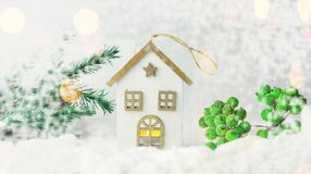 Toy decoration house made of wood on white snow. With branches of Christmas tree on holiday new year and christmas Royalty Free Stock Images