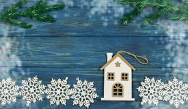 Toy decoration house made of wood on white snow. With christmas tree branches on holiday new year and christmas on blue wooden texture background Royalty Free Stock Image
