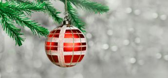 Toy decoration red ball with white pattern. Near fir tree branches on a Christmas tree on a bright bokeh background Royalty Free Stock Photos