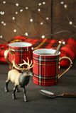 Toy deer with mugs on rustic holiday background stock images