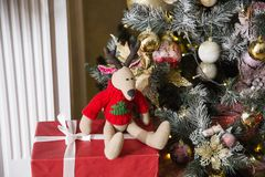 Toy deer in a New Year`s interior together with a red gift against the background of a fir-tree stock photography