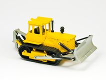 Toy digger. Small model bulldozer isolated on white background Stock Photos