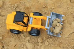Toy digging machine on the sand Royalty Free Stock Photography