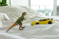 Toy dinosaur and car on parent`s bed stock photo