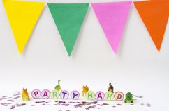 Toy dinosaurs party. Party hard made from colorful letters, toy little dinosaurs and stars confetti on white background royalty free stock photos