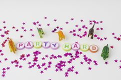 Toy dinosaurs party. Party hard made from colorful letters, toy little dinosaurs and stars confetti on white background stock photo