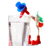 Toy dips by big beak into water in glass. Red toy in blue hat dips by big beak into water in transparent glass Royalty Free Stock Image